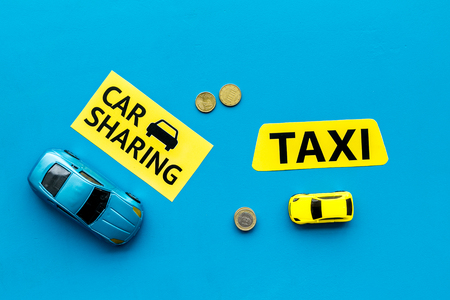 Car sharing vs taxi concept. Comparing car sharing system and taxi. Ship trip concept. Toy cars ans coins on blue background top view space for text
