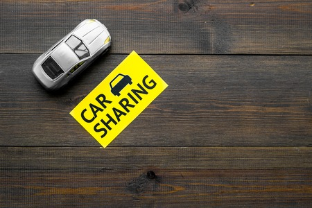 Car sharing concept. Toy car near text car sharing on dark wooden background top view copy space