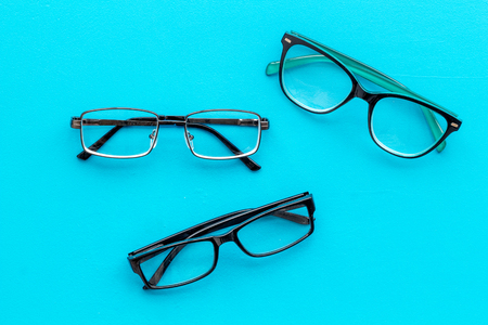 Set of glasses with transparent lenses on blue background top view Stock Photo
