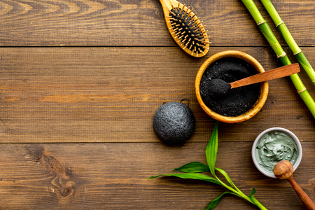 Skin cleansing and detox. Bamboo charcoal powder cosmetics on dark wooden background top view space for text Stock Photo