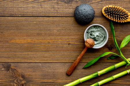 Skin cleansing and detox. Bamboo charcoal powder cosmetics on dark wooden background top view copy space Stock Photo - 117644351