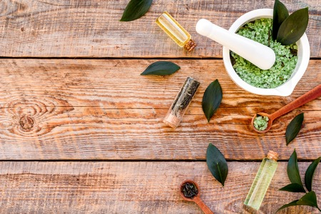 Make cosmetics with tea tree essential oil. Homemade cosmetics. Fresh tea tree leaves, mortar and pestel, cosmetics on rustic wooden background top view border space for text