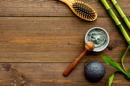 Skin cleansing and detox. Bamboo charcoal powder cosmetics on dark wooden background top view copy space Stock Photo - 117644478