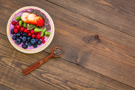 Superfoods. Acai smoothie bowl with fresh fruits, berries, chia seeds on dark wooden background top view copy space