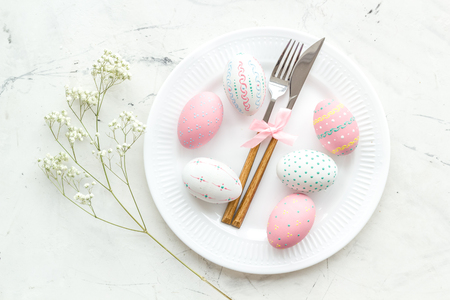 Easter table setting. Tableware and painted eggs on white background top view