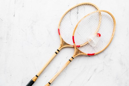 Badminton concept. Badminton rackets and shuttlecock on white stone background top view copy space Stock Photo