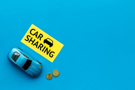 Car sharing concept, car sharing sign. Economical, chip trip. Toy car near coins on blue background top view space for text