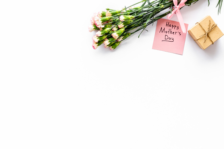 Mothers Day congratulations. Carnations and gift box on white background top view copy space