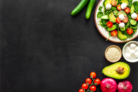 Ingredients for fresh salad. Vegetables, greens, spices, plate of salad on black background top view space for text Stock Photo