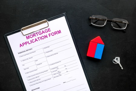 Mortgage concept. Mortgage application form near key and house made of constructor on black background top view