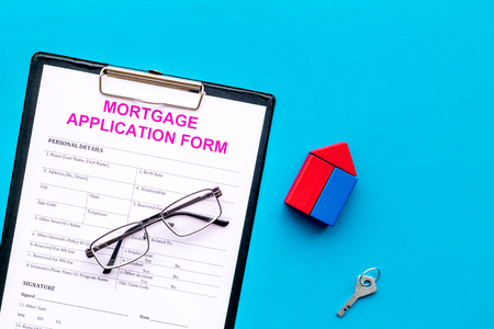 Mortgage concept. Mortgage application form near key and house made of constructor on blue background top view space for text Stockfoto