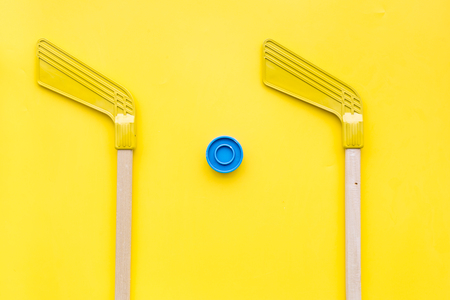 Ice hockey stick and puck on yellow background top view Stock fotó