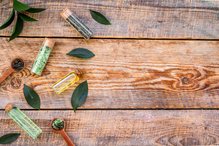 Tea tree oil in small glass bottle near fresh tea tree leaves on rustic wooden background top view space for text border Stock Photo