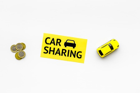 Car sharing concept, car sharing sign. Economical, chip trip. Toy car near coins on white background top view copy space