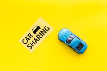 Concept de partage de voiture. Voiture jouet près de l'autopartage de texte sur l'espace de copie de la vue de dessus de fond jaune