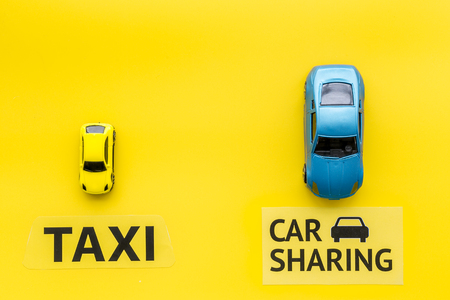 Car sharing vs taxi concept. Comparing car sharing system and taxi. Ship trip concept. Toy cars and text signs on yellow background top view copy space Stock Photo