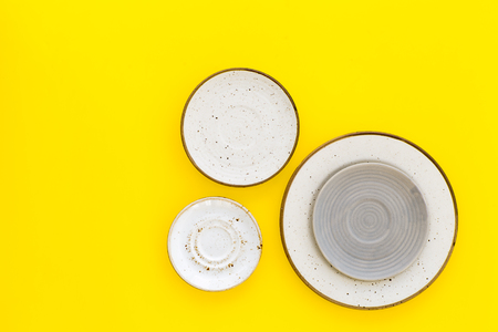 Ceramic plates pattern on yellow background top view space for text Stock Photo