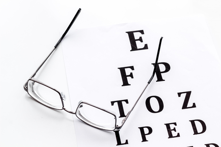Eye examination. Eyesight test chart and glasses on white background Stock Photo