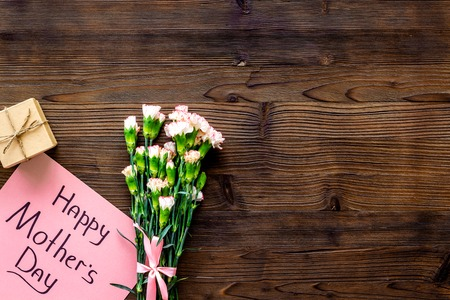 Happy Mothers Day concept. Hand lettering near bouquet of pink carnation and gift box on dark wooden background top view copy space