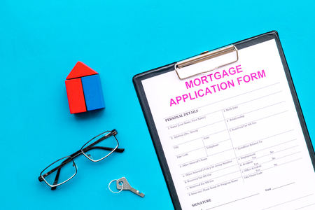 Mortgage concept. Mortgage application form near key and house made of constructor on blue background top view