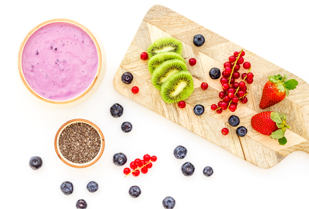 Preparing healthy fruit smoothie. Acai smoothie bowl near cutting board with fresh fruits, berries, chia seeds on white background top view