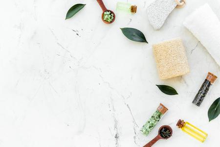 Teebaum-Spa-Komposition. Frische Teebaumblätter, Naturkosmetik, Handtuch auf weißem Steinhintergrund Draufsicht Kopie Raum Grenze