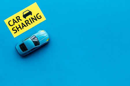 Car sharing concept. Toy car near text car sharing on blue background top view copy space