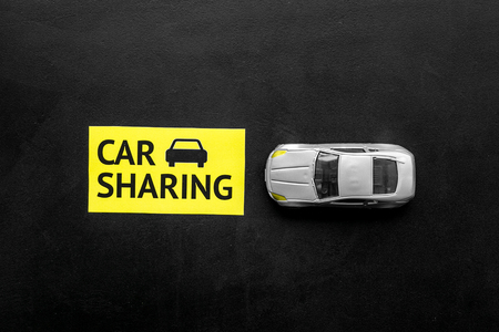 Car sharing concept. Toy car near text car sharing on black background top view space for text Stock Photo