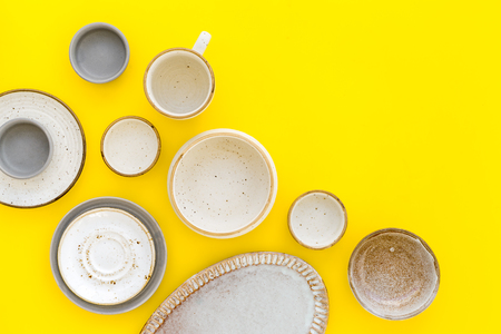 Ceramic tableware pattern. Empty plates and mugs on yellow background top view space for text