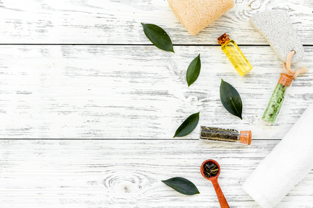 Tea tree spa composition. Fresh tea tree leaves, natural cosmetics, towel on white wooden background top view space for text border Stock Photo