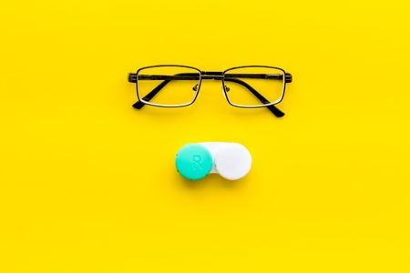 Eyes care. Glasses with transparent lenses and contact lenses on yellow background top view copy space