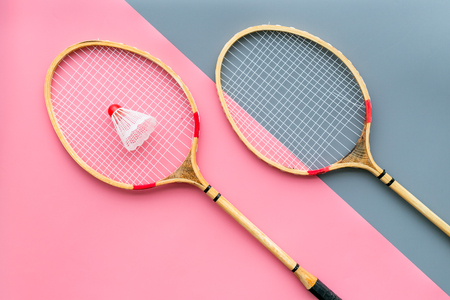 Badminton equipment. Badminton rackets and shuttlecock on pink and grey background top view copy space Stock Photo