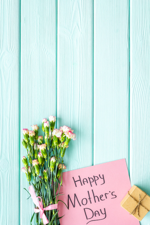 Happy Mothers Day concept. Hand lettering near bouquet of pink carnation and gift box on blue turquoise wooden background top view copy space