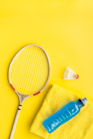 Badminton training concept. Badminton racket, shuttlecock, sport drink and towel on yellow background top view.