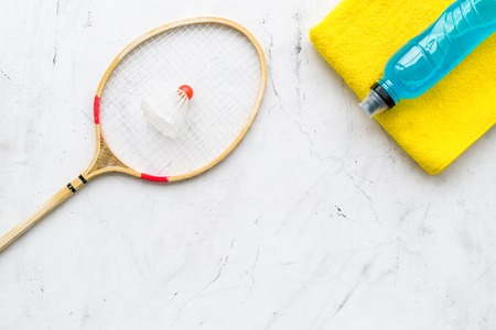 Badminton training concept. Badminton racket, shuttlecock, sport drink and towel on white stone background top view.