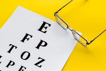 Eye examination. Eyesight test chart and glasses on yellow background. Archivio Fotografico - 117887866
