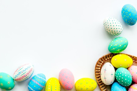 Easter traditions. Colorful Easter eggs in basket on white background top view.