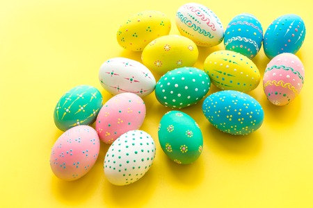 Easter composition. Decorated pastel Easter eggs on yellow background. Stock Photo