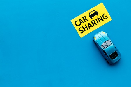 Car sharing concept. Toy car near text car sharing on blue background top view.