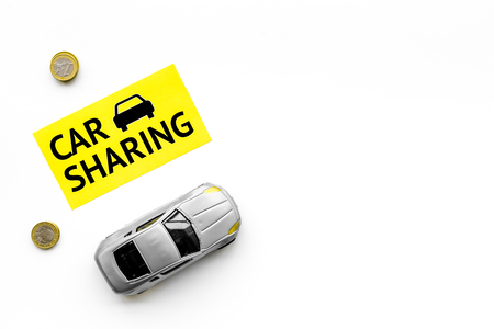 Car sharing concept, car sharing sign. Economical, chip trip. Toy car near coins on white background top view. Stock Photo
