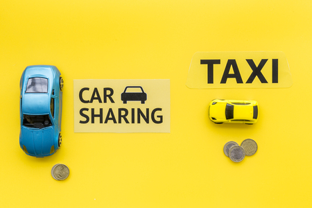 Car sharing vs taxi concept. Comparing car sharing system and taxi. Ship trip concept. Toy cars ans coins on yellow background top view.