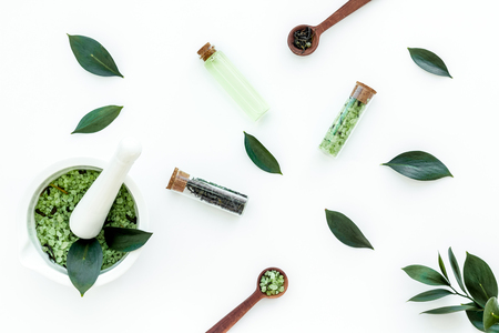 Natural organic cosmetics with tea tree essential oil near fresh tea tree leaves on white background top view.
