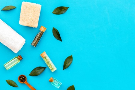 Tea tree spa composition. Fresh tea tree leaves, natural cosmetics, towel on blue background top view.
