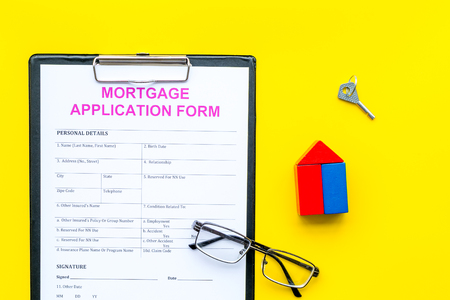 Mortgage concept. Mortgage application form near key and house made of constructor on yellow background top view. Stockfoto