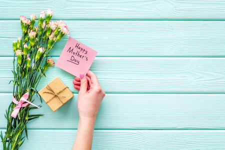 Happy Mothers Day concept. Hand lettering near bouquet of pink carnation and gift box on blue turquoise wooden background top view. Reklamní fotografie