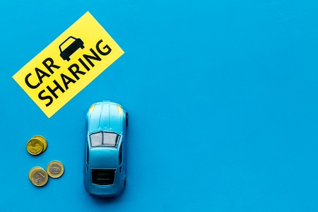 Car sharing concept, car sharing sign. Economical, chip trip. Toy car near coins on blue background top view.