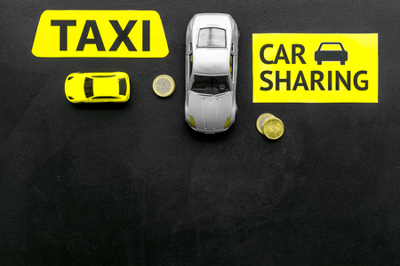 Car sharing vs taxi concept. Comparing car sharing system and taxi. Ship trip concept. Toy cars ans coins on black background top view. Stock Photo