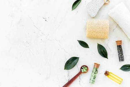Tea tree spa composition. Fresh tea tree leaves, natural cosmetics, towel on white stone background top view copy space border Stock Photo