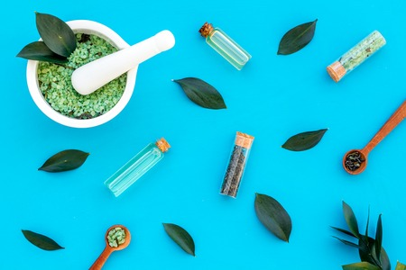 Make cosmetics with tea tree essential oil. Homemade cosmetics. Fresh tea tree leaves, mortar, cosmetics on blue background top view pattern Stock Photo