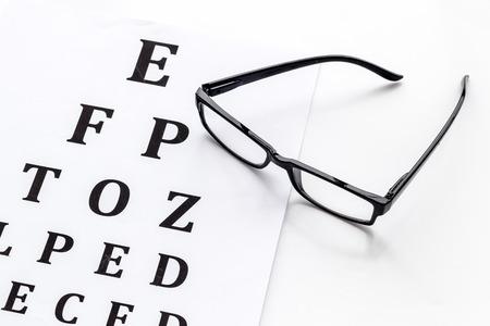 Examen de la vista. Tabla de prueba de la vista y gafas sobre fondo blanco. Foto de archivo